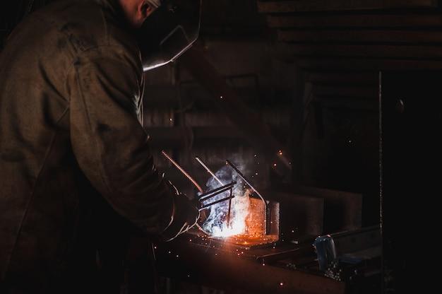 溶接工の仕事。大規模なコンクリート製品工場とその溶接。