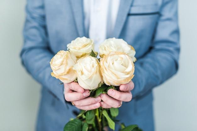 手に白いバラの花束。バレンタイン・デー