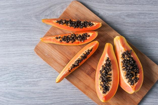 Папайя на деревянных фоне. здоровая пища, спелые экзотические фрукты