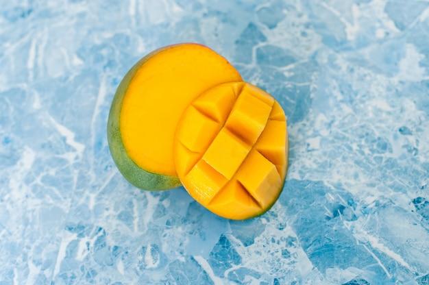 青色の背景にマンゴー。エキゾチックな果物を切る方法