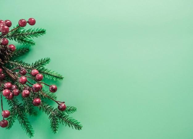 赤い果実と美しいミントの背景にモミの枝のクリスマスの装飾。