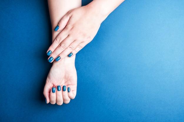 Красивый женский маникюр стильного синего цвета. концепция зимних оттенков для ногтей, уход за собой. пространство для текста