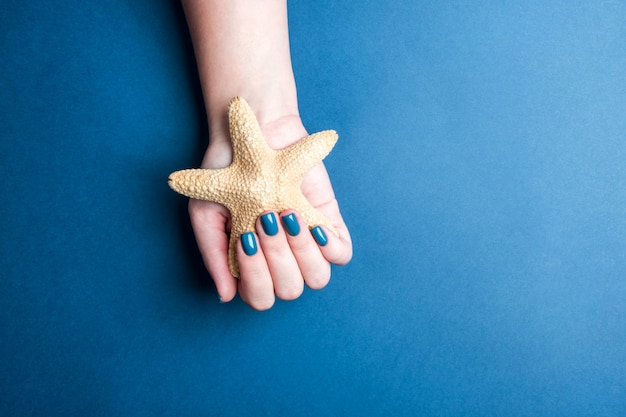 美しい女性のマニキュアスタイリッシュな青い色。爪の冬の色合いの概念、休日の前に自分自身をケア、航海のテーマ、テキストのための場所