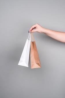 灰色の壁にクラフト紙で作られたショッピングバッグとギフトバッグ。廃棄物ゼロのコンセプト