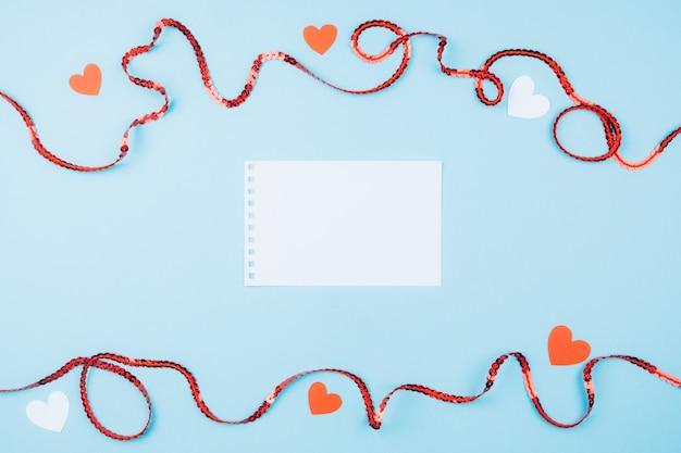 テキスト用のスペースと美しい青色の背景。赤いリボンとハート。バレンタインデーのコンセプト