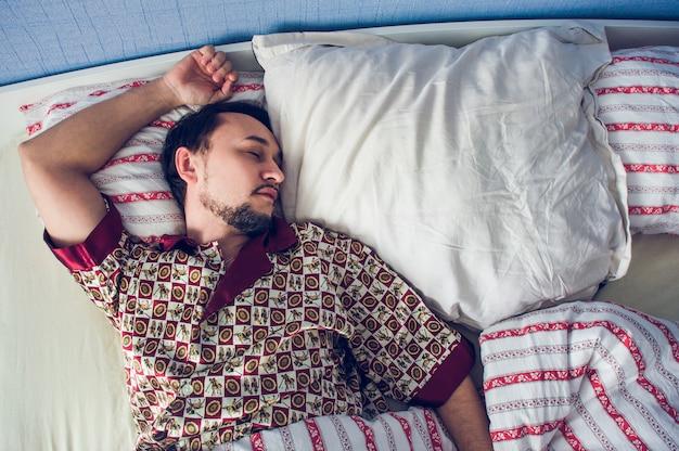 Человек спит в своей постели на белой подушке