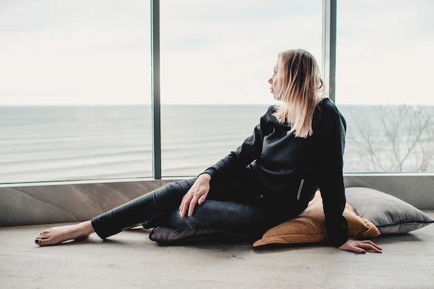 Грустная женщина, сидя у большого окна с видом на море в пустой квартире. изоляция, одиночество, грусть.
