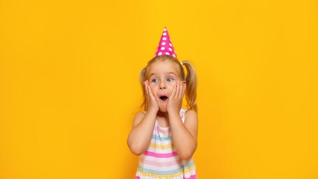 色付きの黄色の背景にピンクの帽子で幸せな誕生日の子女の子。幼児は驚いた顔で頬を抱えています。