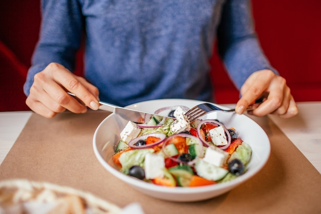 木製のテーブルに自宅で野菜のギリシャ風サラダを食べる若い女性のクローズアップ