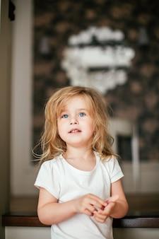青い目を持つ少し毛むくじゃらの金髪の赤ちゃん女の子は彼女の朝目覚めた後笑っています。
