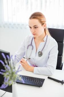 Портрет серьезного молодого женского белокурого доктора используя компьютер в ее офисе