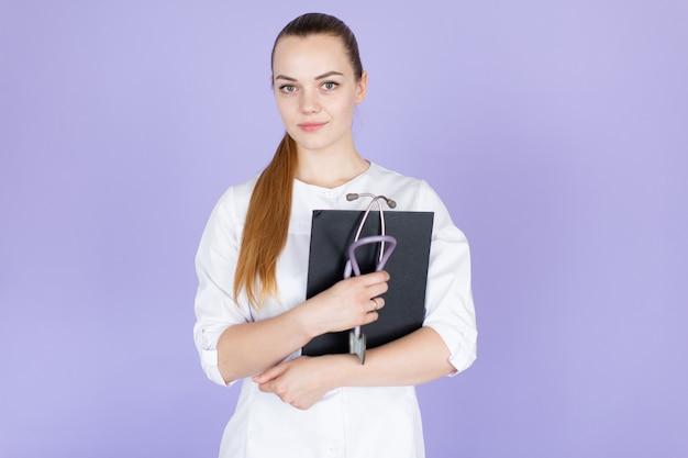 彼女の首に聴診器で長い髪のポニーテールと若い笑顔金髪女性医師。