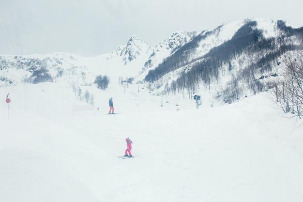 冬の雪の下の高山。スキーリゾート。スキーヤーは山から降りる
