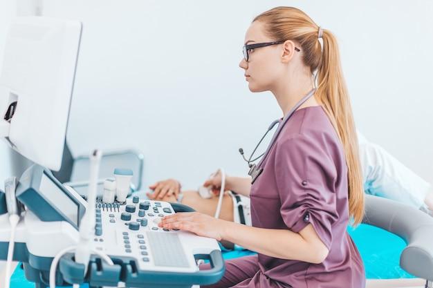 黒いメガネを持つ若い女性の孤独な医者。医者の手に超音波スキャナー。診断超音波検査