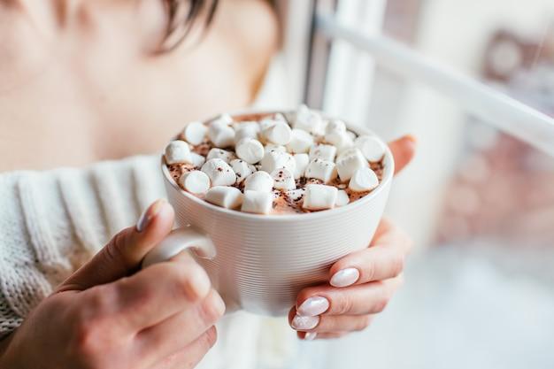 白いセーターの女の子は、マシュマロとホットチョコレートのカップを保持し、窓の近くにとどまる彼女の手を温めます。