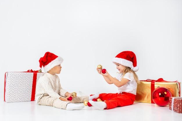 ギフトボックスの間に座って、クリスマスボールで遊ぶサンタ帽子で面白い小さな子供たち。白い壁に分離されました。新年