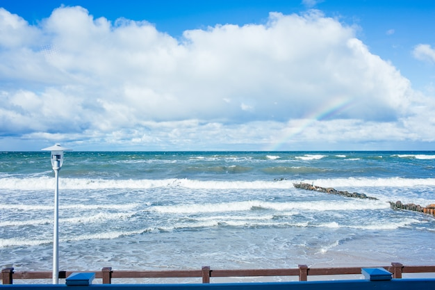 青い海、美しい白い雲、晴れた秋の日に虹とバルト海のビーチ風景。