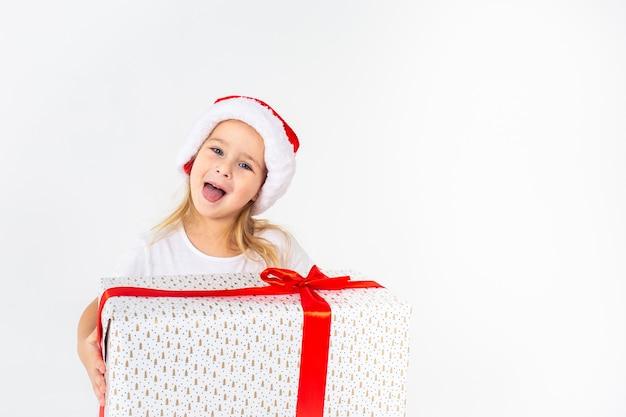 白い分離壁に赤いリボンと白いギフトを保持しているサンタヘルパー帽子で少し微笑んでいる女の子。クリスマス、冬、幸福の概念。