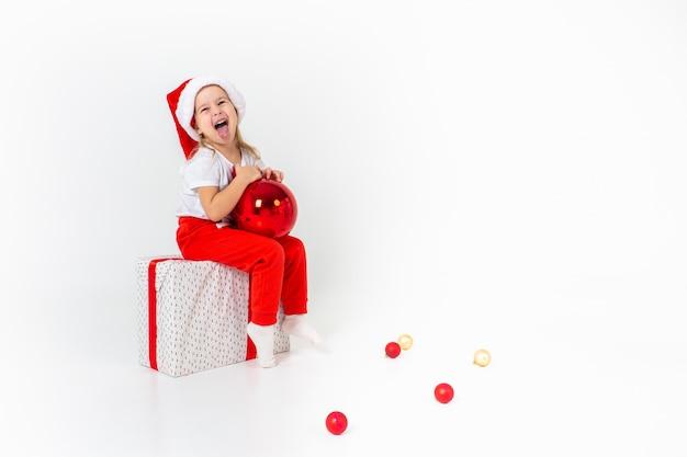 赤いリボンとギフトボックスの上に座って、赤いクリスマスボール、白い分離壁を保持しているサンタヘルパー帽子に笑みを浮かべて少女。クリスマス、冬、幸福の概念。