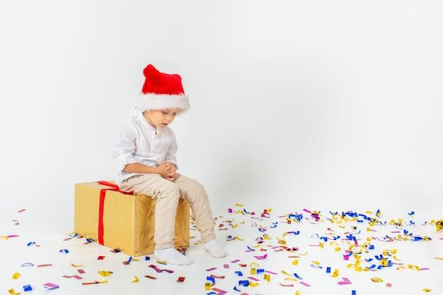 赤いリボン、白い分離壁、紙吹雪とギフトボックスの上に座ってサンタヘルパー帽子の悲しい少年。クリスマス、冬、新年のコンセプト。