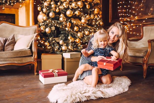 Мать и дочь в блестящей одежде обниматься и улыбаться, зимний вечер вместе дома в украшенной гостиной в канун рождества.