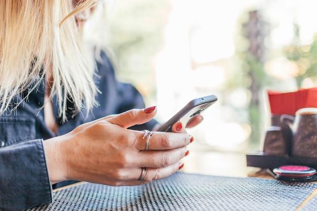 カフェで携帯電話とテーブルを保持している女性の手のクローズアップ。コーヒーブレーク中に携帯電話でビデオを見ている女の子やソーシャルネットワークを使用している女の子