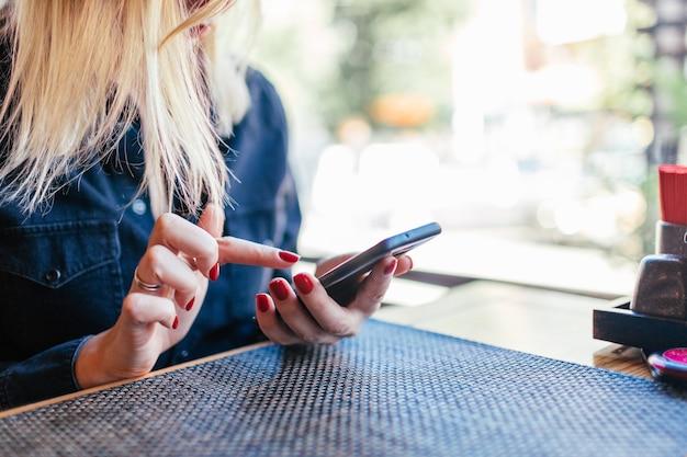 Женские руки держат сотовый телефон и столик в кафе.