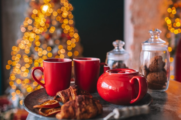 Красный чайник с двумя красными чашками на подносе с сухим апельсином и круассаном. огни елки фона. дух рождества, уютный дом