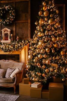 ライトと黄金の装飾とリビングルームの暖炉のあるクリスマスツリー。