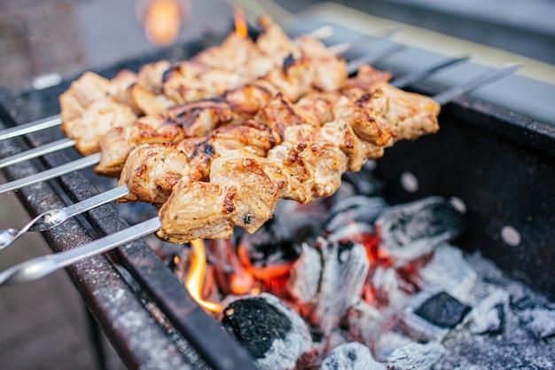 ソースと肉のジューシーなスライスは火シシカバブに準備します。外でバーベキュー。