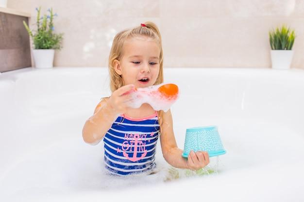 美しいバスルームで泡風呂に入っている金髪少女。子供の衛生。子供用のシャンプー、ヘアトリートメント、石鹸。大きな浴槽での子供の入浴。