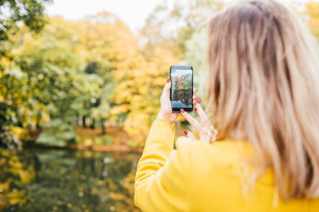 Белокурая женщина оно желтое пальто делает фото на сотовом телефоне в парке в осени. закройте вверх, селективный фокус.