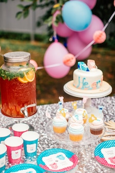 男の子または女の子のケーキと屋外のテーブルでベビーシャワーパーティーのさまざまなお菓子