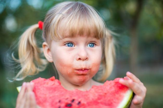青い目をした愛らしいブロンドの女の子は屋外スイカのスライスを食べる