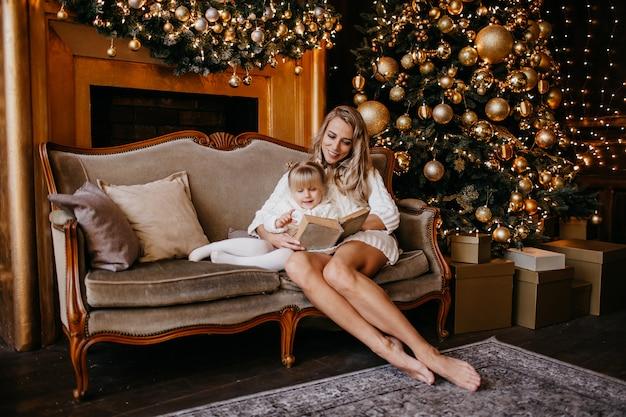 母と娘はクリスマスイブに暖炉のそばで本を読んでいます。装飾されたリビングルームには、木、暖炉、ギフトがあります。両親と子供のための家での冬の夜。