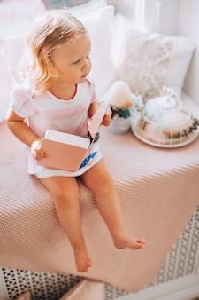 窓辺にピンクの本とピンクのドレスでかわいい小さな巻き毛のブロンドの女の子。