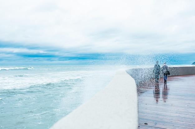 曇りの秋の雨の日に桟橋の道をはねかける大きな海の波と怖い嵐の波。高波は桟橋で壊れています。二人が桟橋の上を歩いています。