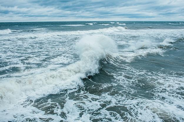 Волны разбиваются и распыляются в открытом море и при сильном ветре. буря на море в осенний пасмурный дождливый день.