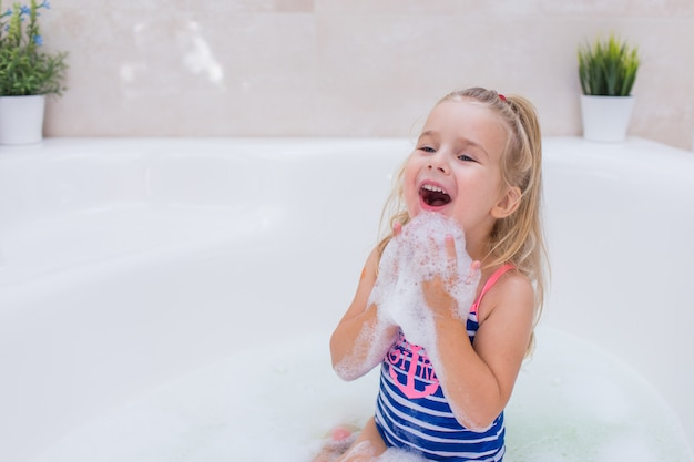 Маленькая белокурая девушка принимая жемчужную ванну в красивой ванной комнате. детская гигиена. шампунь, лечение волос и мыло для детей. малыш купается в большой ванне.