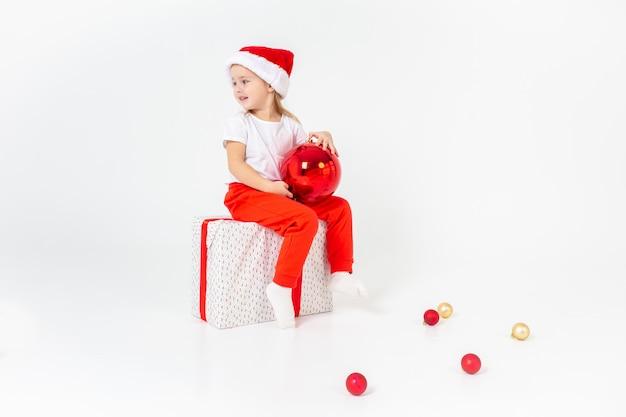 赤いリボンとギフトボックスの上に座って、赤いクリスマスボール、白い分離背景を保持しているサンタヘルパー帽子で少し微笑んでいる女の子。クリスマス、冬、幸福の概念。