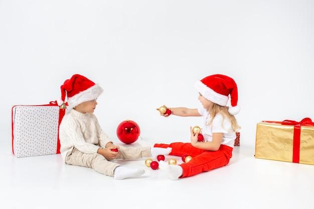 ギフトボックスの間に座って、クリスマスボールで遊ぶサンタ帽子で面白い小さな子供たち。白い背景に分離します。新年