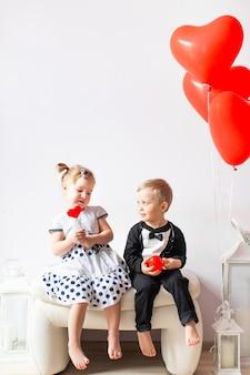 小さな女の子と男の子のハート形の風船の近くの白い椅子に座っています。赤いロリポップを舐めている女の子。バレンタインデーのコンセプト。