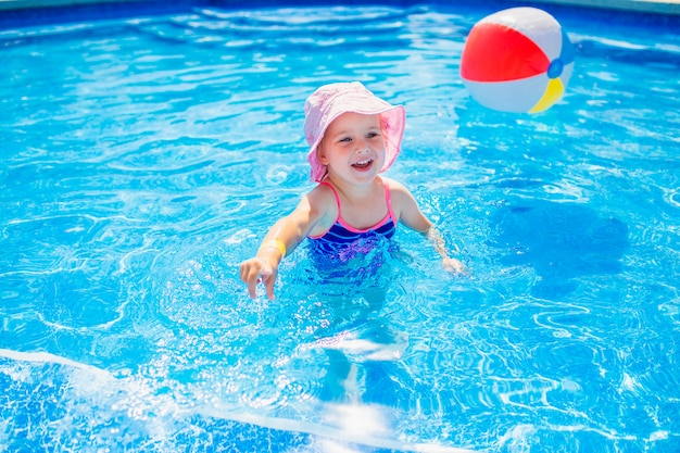 Плавание, летние каникулы - милая улыбающаяся девушка в розовой шляпе и синем купальнике играет в голубой воде с надувным разноцветным шариком в бассейне