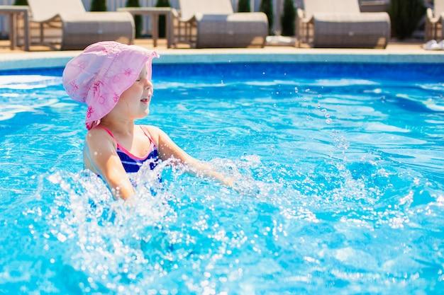 Плавание, летние каникулы - милые улыбающиеся девушки в розовой шляпе и синий купальник, играя в голубой воде в бассейне.