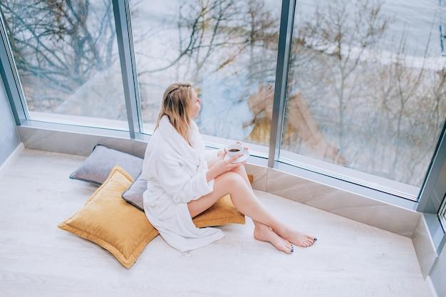 一杯のコーヒーと大きな窓の横にある海の景色を楽しみながら白いバスローブの女性。パノラマ窓。床材、ホテルでの休暇