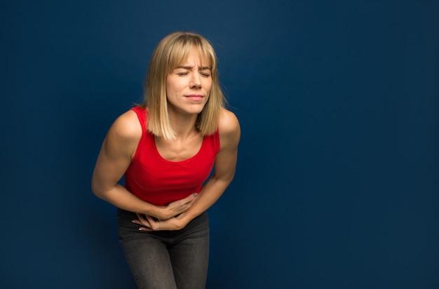 消化不良、痛みを伴う病気の気分が悪くなるため、胃に手を持つ若い美しい女性。痛みの概念。