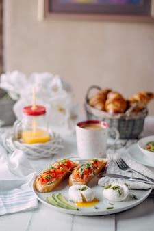 ノルウェーの朝食。サーモン、サラダ、コーヒー、オレンジジュース、クロワッサンと白い木製テーブルでゆで卵とトースト