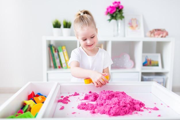 Маленькая белокурая девушка играя с розовым кинетическим песком на белой таблице в светлой комнате. сенсорное развитие. уроки в детском саду.