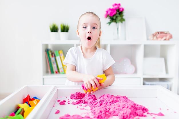 Маленькая белокурая девушка с удивленным лицом играя с розовым кинетическим песком на белой таблице в светлой комнате. сенсорное развитие.