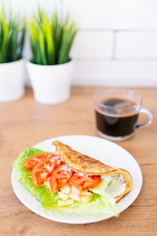 スペースにコーヒーのカップを持つ木製のテーブルに滞在している緑の葉とクリームチーズ、チーズ、トマトを詰めた白い皿にオート麦パンケーキ。健康食品